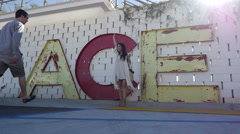 Stock Video Footage of Couple Poses in front of ACE sign