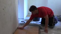 Stock Video Footage of man glue ceramic tile on kitchen floor at home