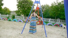 Mom rolls on child swing, playground, swing Stock Footage