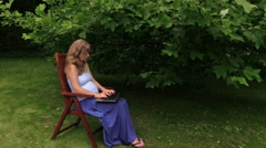 Pregnant woman working with computer in shade of tulip tree Stock Footage