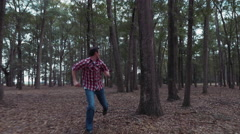 Scared man running through forest Stock Footage