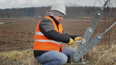Stock Video Footage of Worker with  adjustable wrench near tensioner on field