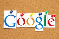 Google logotype printed on paper, cut and pinned on cork bulletin board. - stock photo