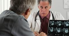 Doctor discussing elderly patient's mri scans - stock photo
