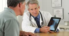 Doctor consulting senior patient about his xrays Stock Photos