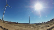 Stock Video Footage of Sun Over Rotating Electricity Producing Wind Turbines