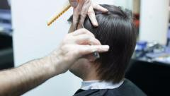 Hairdresser cuts male hair with scissors Stock Footage