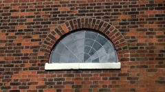 Leaded window semi circular red brick lunette Stock Footage