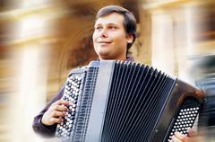 Stock Photo of Male playing on the accordion against a grunge background