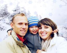 Stock Photo of Happy family portrait outdoors smiling. Winter