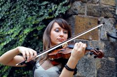 Stock Photo of Playing violinist on the grunge background