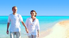 View of happy young couple walking on the beach, holding hands. - stock photo
