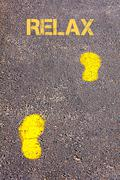Yellow footsteps on sidewalk towards Relax message, Leisure conceptual image. - stock photo
