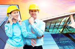 Young architects wearing a protective helmet standing on the bui - stock photo