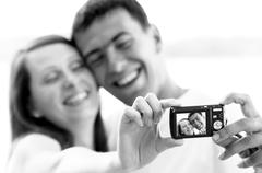 Stock Photo of An attractive couple together on the white background, taking a