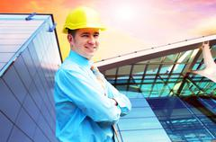 Stock Photo of Young architect wearing a protective helmet standing on the buil
