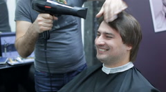 Happy man in barber shop drying hair with hairdryer Stock Footage
