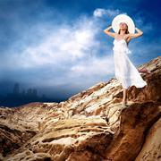 Beautiful girl in White on the mauntain under sky with clouds - stock photo