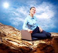 Stock Photo of Happy Businesswoman seating with laptop on the mountain under bl