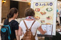 Tourists looking at menu in front of the restaurant terrace. - stock photo