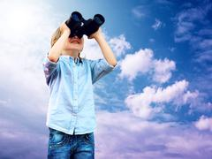 Stock Photo of Young boy watch in the field-glass, outdoors.