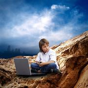 Stock Photo of Child with laptop on the mauntain under sky with clouds