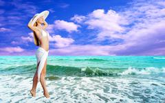 Young beautiful women in the white on the sunny tropical beach Stock Photos