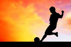 Silhouettes of footballers on the sunset sky - stock photo