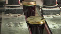 Jars of strawberry preserves moving through food facility Stock Footage