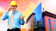 Young architect wearing a protective helmet standing on the buil - stock photo
