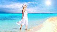 Stock Photo of Young beautiful women in the white on the sunny tropical beach