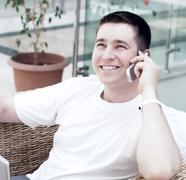 Stock Photo of Smiling young man working on laptop computer and call by phone a