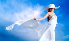 Stock Photo of Young beautiful women in the white with pareo on the blue sky ba