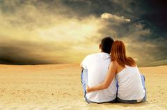 Stock Photo of Young couple seating in desert in sunny day