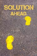 Yellow footsteps on sidewalk towards Solution Ahead message Stock Photos