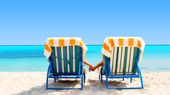 Rear view of a couple on a deck chair relaxing on the beach Stock Photos