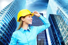 Young architect-woman wearing a protective helmet standing on th - stock photo