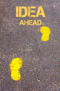 Yellow footsteps on sidewalk towards Idea Ahead message Stock Photos