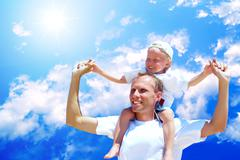 Stock Photo of Joyful father giving piggyback ride to his son against a sky bac