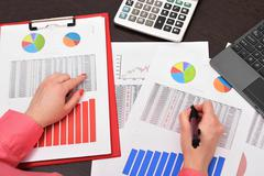 businesswoman analyzing investment charts - stock photo
