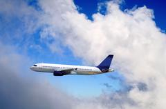 Stock Photo of Airplane at fly on the sky with clouds