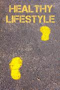 Yellow footsteps on sidewalk towards Healthy Lifestyle message Stock Photos