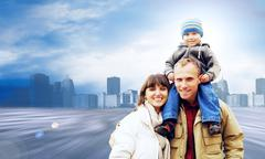 Stock Photo of Happy family portrait outdoors smiling on the road in city