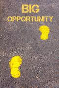 Yellow footsteps on sidewalk towards Big Opportunity message - stock photo