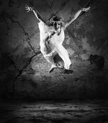 Woman dancer jump posing on background - stock photo