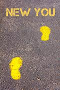 Yellow footsteps on sidewalk towards New You message - stock photo