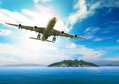 passenger plane flying over beautiful blue ocean and island in purity destina - stock photo
