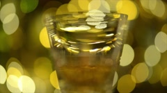 Abstract defocussed view of whisky glass infront of bokeh lights Stock Footage