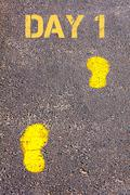 Yellow footsteps on sidewalk towards Day 1 message Stock Photos