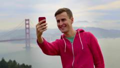 Man Takes A Selfie With The Golden Gate Bridge In The Background Stock Footage